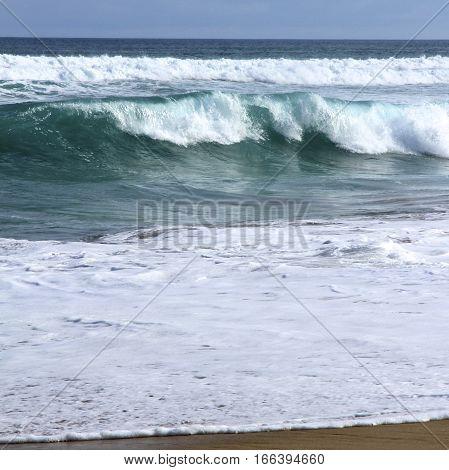 Blue green water breaking on a beach.