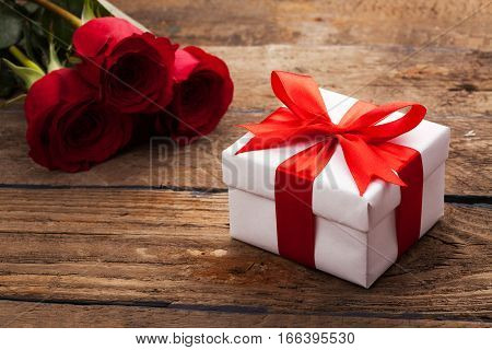 Red roses and gift box on a wooden background
