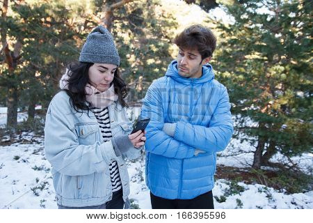 Young caucasian white woman chatting with mobile phone as she passes from her boyfriend in the snow. The couple is on a date in the mountains on a snowy day.