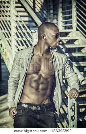 Portrait of a hot black man in sunglasses with visible abs posing for camera