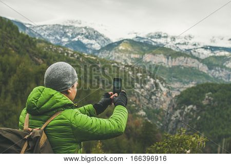 Young man traveller wearing bright clothes making photo of mountains with snowy peaks in Dim Cay district of Alanya on gloomy day, Antalya province, Mediterranean Turkey