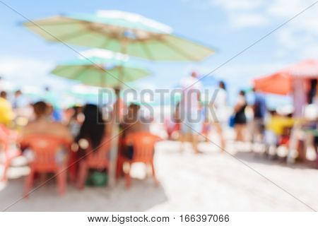 Blurred background photo of people on the beach having fun under umbrellas