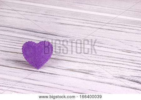 Purple felt heart on a white wooden background. Valentine Day.Greeting card.Wedding