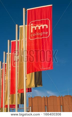 Cologne, Germany - January 22, 2017: imm Cologne - international exhibition of furniture and interior design. Flags at the main entrance to the exhibition Koelnmesse. Flags at imm company colors - red and gold.