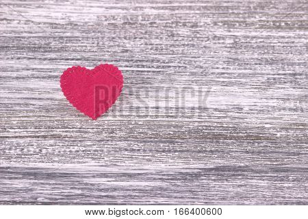 Red heart of felt on a gray wooden background. Valentine Day.Greeting card.Wedding