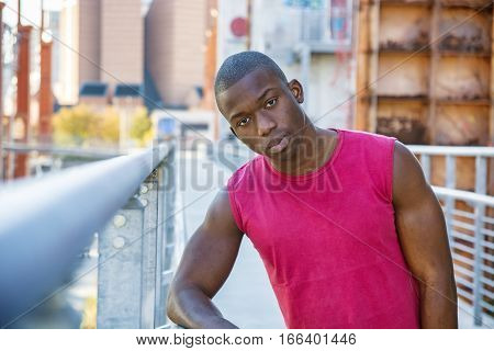 Portrait of a sexy young black man in urban environment wearing red sleeveless shirt