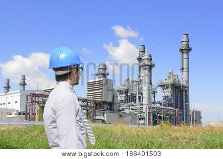 The enginerr man who looking at gas turbine power plant for industrial park with the blue sky