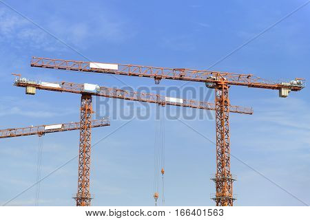 The red arm of the construction crane with the blue sky.