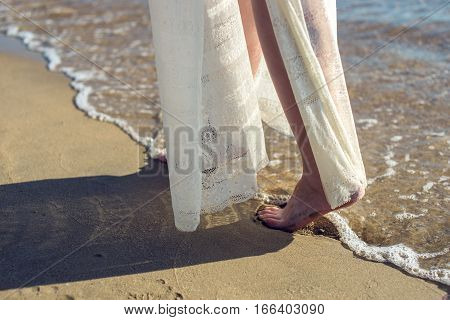 Girl Walks Barefoot On The Sand In A White Dress
