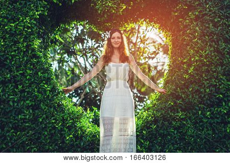 Woman Standing On Background Of Green Bushes Shape Like Heart