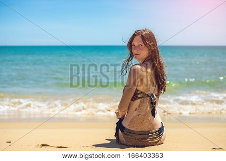 Woman Sitting On Beach And Looking At Blue Sea