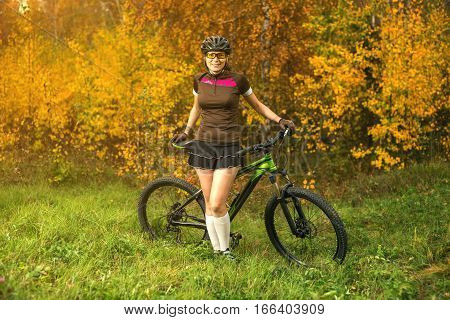 Woman Biking In Yellow Autumn Forest On A Meadow