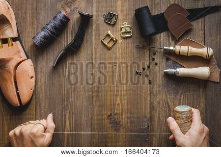 cobbler tools in workshop on dark background top view with hands