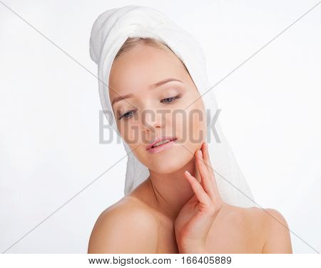 Beauty Woman face Portrait in a towel. Beautiful Blonde Spa model Girl with Perfect Fresh Clean Skin. Skin Care Concept Isolated on a white background
