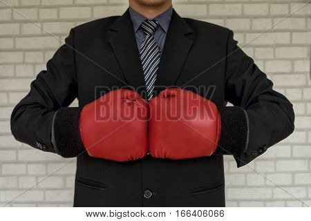Businessman in suit with with boxing gloves tough competitive business concept business concept vintage tone soft focus