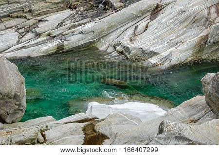 Fast flowing cold emerald water between the water-polished rocks in the Val Verzasca river in Switzerland