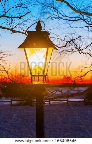 Illuminated Old Street Lamp In Winter Landscape
