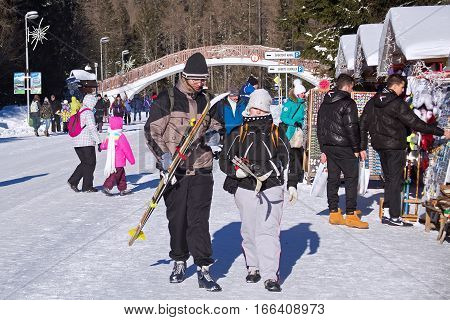 SLOVAKIA, STRBSKE PLESO - JANUARY 06, 2015: Skiers and other active tourists in Strbske Pleso. The village is a favorite ski tourist and health resort in the slovakian part of High Tatras mountains.