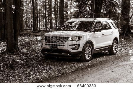 Pocono Lake, Pennsylvania, July 6, 2016: A white 2016 Ford Explorer is parked by a dirt road in a wooded area.