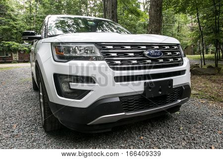Pocono Lake, Pennsylvania, July 7, 2016: A white 2016 Ford Explorer is parked on a gravel driveway in a forested area.