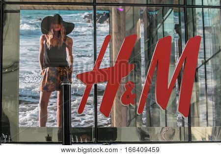 New York, July 19, 2016: Large red H & M letters on a glass wall obstruct a view inside the popular clothing store. A big screen is seen on the background.