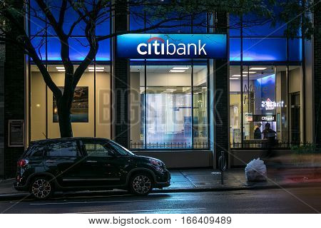 New York, July 25, 2016: The sign is lit up on a Citibank branch in Manhattan with a car parked in front of it.