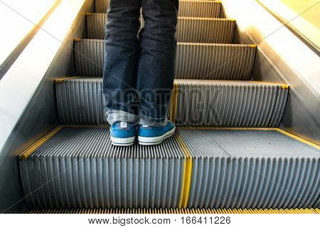 Close up Men wear jeans on escalator to up