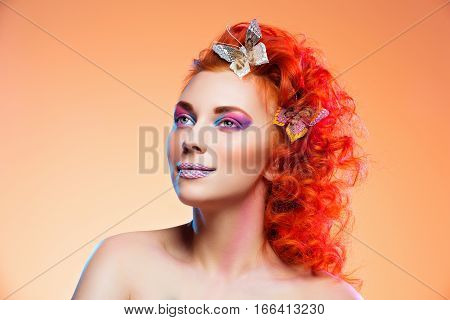 Beautiful young red haired woman with bright colorful makeup and butterflies in hair over orange background. Portrait beauty shot. Copy space.