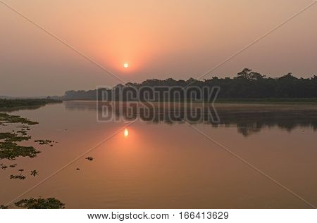 Sunrise on on the Quiet waters of the Rapti River in Chitwan National Park in Nepal