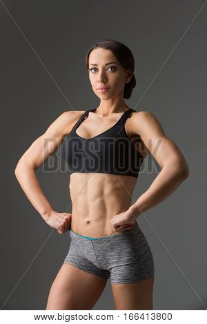 Beautiful fit muscular young woman in sport bra and shorts over grey background. Perfect body. Studio shot.