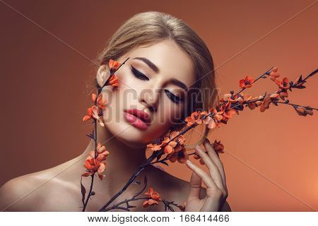 Beautiful young woman with make-up and loose hairdo holding artificial sakura branch with orange flowers. Beauty shot on brown background. Copy space.