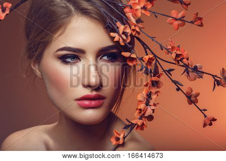Beautiful young woman with make-up and loose hairdo with artificial sakura branch with orange flowers. Beauty shot on brown background. Copy space.