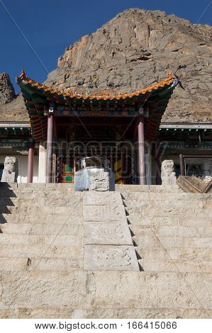 Exterior of the Buddhist Arayabal Meditation Temple in Gorkhi-Terelj National Park in Mongolia with stone steps leading to the hand painted wooden canopy over the entrance. Stone statues flank the entry and rugged stone mountains are in the background. De