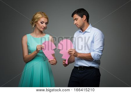Beautiful young couple holding big pink broken heart. Blond woman in mint dress and handsome man in shirt and trousers standing on grey background. Valentine's day concept. People in love. Copy space.