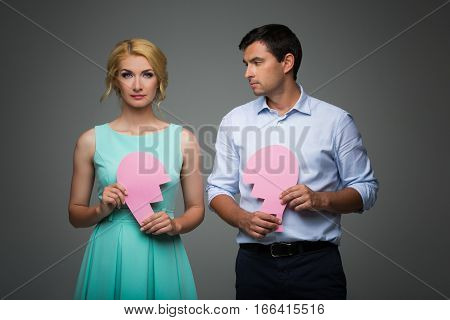 Beautiful young couple holding big pink broken heart. Blond woman in mint dress and handsome man in shirt and trousers standing on grey background. Valentine's day concept. Copy space.