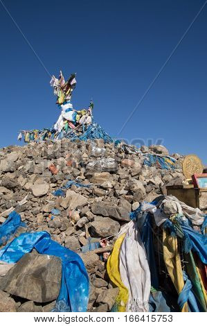An ovoo built from stones placed by worshipers with a branch covered with blue scarves and flags at the top. Scarves and offerings are seen in the foreground. Deep blue sky above. Photographed in Mongolia.