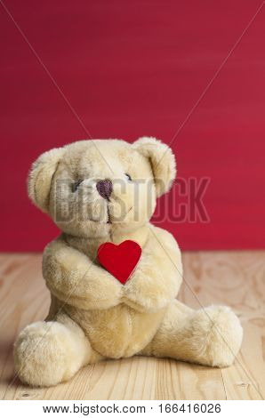Little bear hold red heart in front red grunge background on wooden table. Valentines concept.