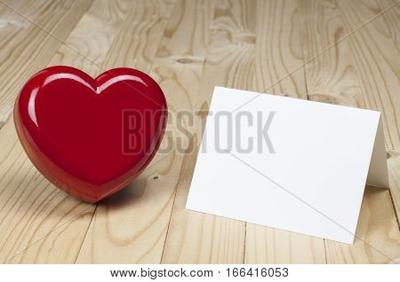 Red heart beside white blank card. Valentines and Love concept.