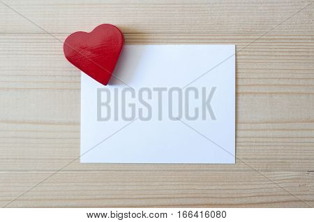 Red heart with blank card on wood. Love and Valentines concept. White blank card.