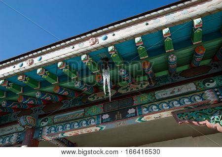 Close up of the hand painted beams, eaves and carved wooden supports on the roof of the Buddhist Arayabel Meditation Temple in Mongolia. Artists have painted colorful floral and geometric designs. Icicles hang from the eaves. Deep blue sky above.