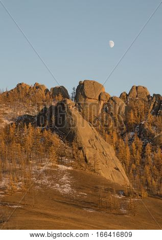 Rugged stone mountains with sparse vegetation with a rose and rust colors in the setting sun. The rising moon is above. Photographed in Gorkhi-Terelj National Park, Mongolia.