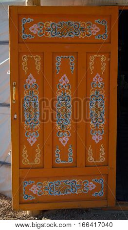 Close up on the interior side of a orange paneled door in a yurt that has been hand painted with elaborate scroll patterns. Photographed in Mongolia.