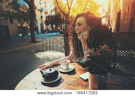 Laughing beautiful white caucasian girl with black curly hair and teal ring sitting in street cafe next to wooden table with cup and teapot of tea sunny summer day in Barcelona Born district Spain