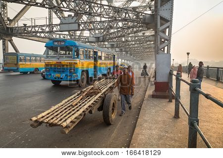 KOLKATA, INDIA - DECEMBER 18, 2016: City morning traffic on Howrah bridge on river Hooghly with people and public transport vehicles going about their daily scores.