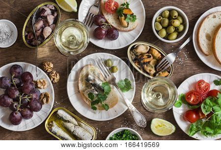 Seafood snacks table - canned sardines mussels octopus grape olives tomato and two glasses white wine on wooden table top view. Flat lay