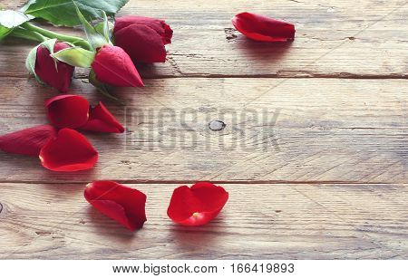 valentine's day three red roses and scattered petals on the old wooden table