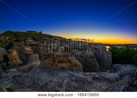 Golden sunrise over the Hoodoo badlands at Writing on Stone Provincial Park and Áísínai'pi National Historic Site in Alberta Canada. The area contains the largest concentration of First Nation petroglyphs (rock carvings) and pictographs (rock paintings).