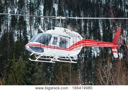 The Helicopter Landed In The Mountains In Winter, Raising A Cloud Of Snow