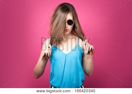 Beautiful fashionable woman in black sunglasses. Pink background. Girl in sunglasses. Round glasses.