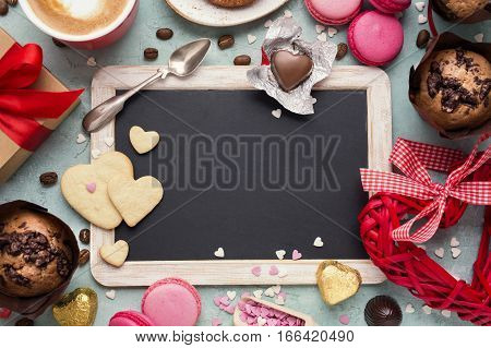 Valentine's Day background with copyspace. Vintage blackboard and sweets. Toned.